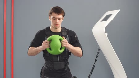 forte : Fit Man in EMS suit training with medecine bal, Stock Footage