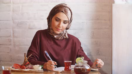 working together : Muslim Business Woman Working Documents in Cafe.