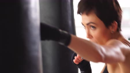 kickbox : Attractive Female Boxer Training Punching a Heavy Bag in the Gym.
