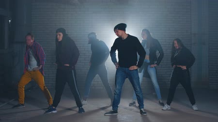 biodro : Group of street dancers performing different moves on the dark street.