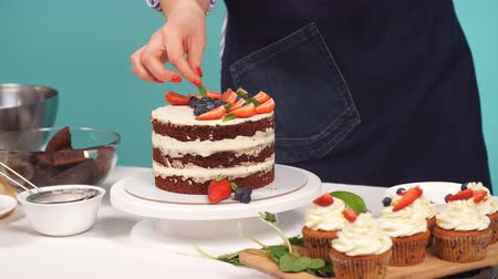 süslemek : Cafe chef decorates a cake. Cake with strawberries and custard. Stok Video