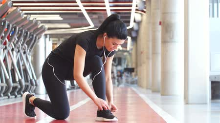 cipőfűző : Girl down to do shoelaces at fitness gym before running exercise workout