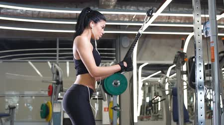 sağlam : Sports woman doing exercise at crossover machine in gym Stok Video
