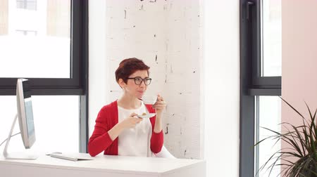 vstup : Young female businessman with coffee Cup at table in modern office.