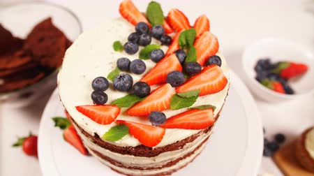 украшать : Beautiful modern cake with white filling decorated with berries and strawberries.