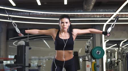 sağlam : Girl in sportswear working out and training shoulders with exercise machine crossover in gym
