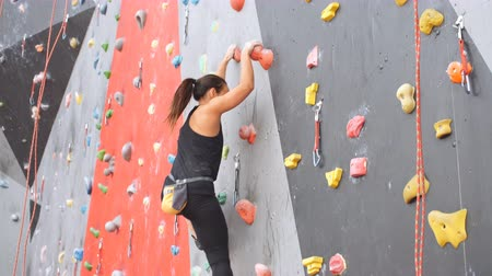 bouldering : Women climbing on a wall in an outdoor climbing center.
