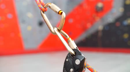 bouldering : Carabiner hook with a climbing rope on rocky background. Climbing concept.