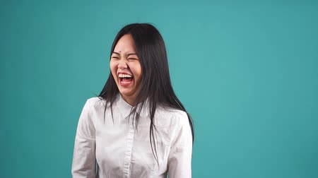 arcszín : Young amazing asian pretty woman looking camera isolated and laughing.