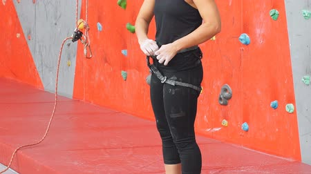 bouldering : Pretty caucasian woman puts on belaying harness for practice on artificial rock wall outdoors. Slim strong healthy blonde prepares to conquer climbing gym wall.