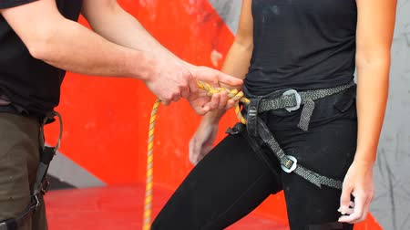 bouldering : Portrait of beautiful man rock climber belaying another climber with rope. Indoors artificial climbing wall and equipment Stock Footage