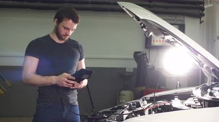 inspectie : Young Technician Man Making Engine Service of Car in Garage.