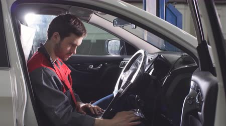 zkoumat : Young Technician Man Making Engine Service of Car in Garage.