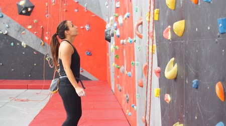 bouldering : Active young woman on rock wall in sport center.