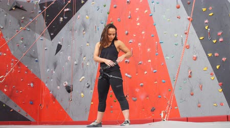bouldering : Portrait of woman on artificial exercise climbing wall. Stock Footage