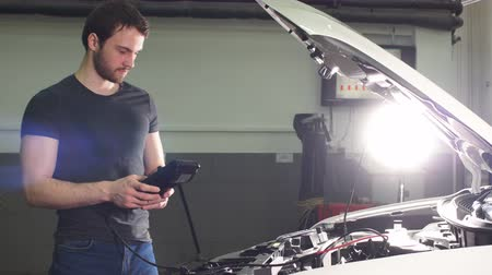 zkoumat : Adult Man Checks the Condition of the Vehicle in a Tire Service Shop. Dostupné videozáznamy