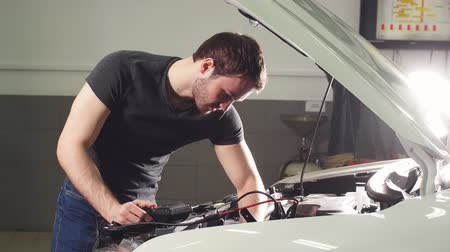 examinando : Young Technician Man Making Engine Service of Car in Garage.