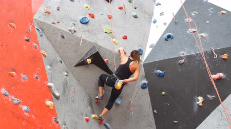 altura : Portrait of woman on artificial exercise climbing wall. Stock Footage