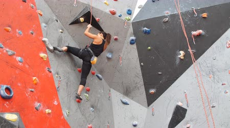 bouldering : Young girl is posing before climbing wall. Stock Footage