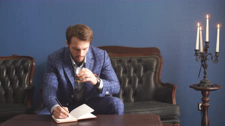 セクシャル : Handsome young man in a classic suit drinking whiskey in restaurant and makes notes in a notebook.