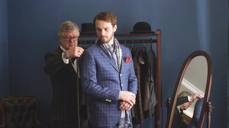 zvyk : Tailor with client in atelier. Sewing custom made suit.