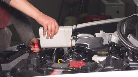 engine oil : Pouring oil to car engine, close up. Stock Footage