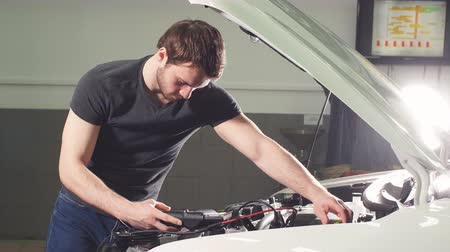 denetleme : Car Mechanic Is Standing in an Auto Repair Shop Near Automobile with Open Hood and Making Notes.