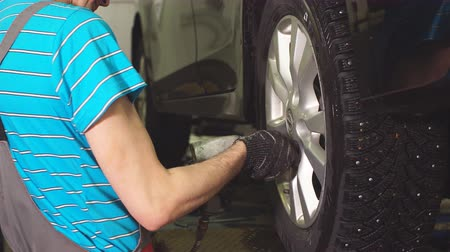 kabarık : Auto Mechanic Is Twisting Bolts of a Wheels on an Automobile, Raised By Lifting Equipment.