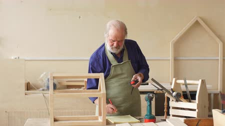 çabaları : Old grey haired carpenter with moustache and beard measuring wooden doll house.