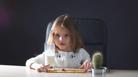 przedszkolak : Happy beautiful little girl having a snack with milk and cookies Wideo