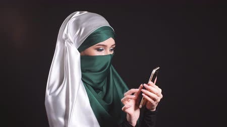islámský : Portrait of happy muslim woman using mobile phone.