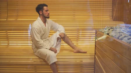 rejuvenescimento : Young handsome man in white robe is heated in the sauna.