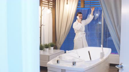 therapeutic : Young attractive man in white robe resting in a luxury Spa center. Man standing at the panoramic window and talking on a mobile phone. Stock Footage
