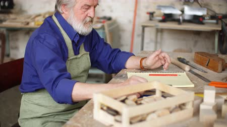 çabaları : Concept of diy. Old man is making a sketch of birds house from wood.