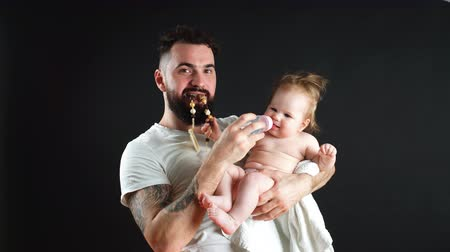 bottle feeding : Father holding and taking care of little infant baby, feeding from bottle.