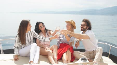 curtimento : Young european tourists guys and girls celebrating on yacht happy start of their vacation - Group of friends toasting drinks and having party on a sailing boat.