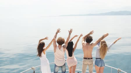 rekreace : Rear view of friends celebrate on sailboat in ocean, arms raised.