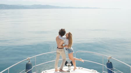 sentimentos : Passionate lovers dancing on bow of deck while sailing on yacht.