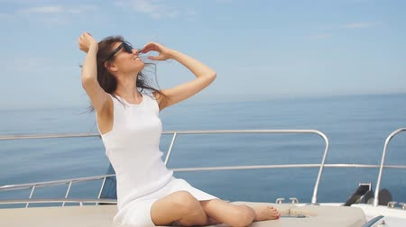 rests : Young attractive and rich woman having fotosession on a luxury boat in sea