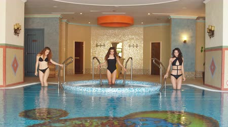 retiro : Beauty and body care. Three Seductive women in stylish swimming suite, relaxing in indoor spa swimming pool at hotel. Refreshment after hot sunny day. Vídeos