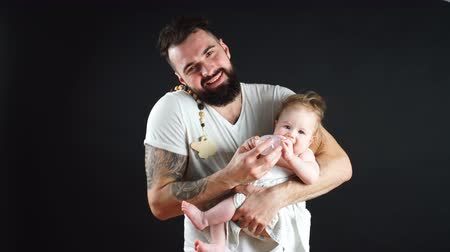 apaság : Adorable caucasian one-year old baby with funny hairstyle, refusing to drink water from nursing bottle Daddy holds. Happy Fatherhood Concept. Stock mozgókép
