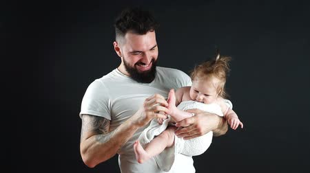 bottle feeding : Adorable baby boy refising drink water from bottle in father hands. White people isolated on black background.