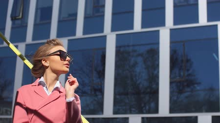 glamorous : Young pretty adventurer in a modern city. Woman runs prosperous business. Low angle shot Stock Footage