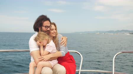 evli : Cute married couple with adorable little daughter looking happy while enjoying romantic trip on the holidays, sailing on sea boat, spending nice time together outdoors. Happiness, sea travelling