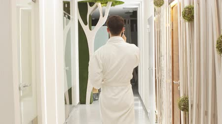 therapeutic : Young man in white robe walks down the hall of luxurious Spa center talking on mobile phone