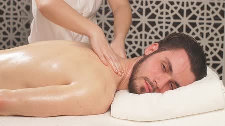 shiatsu : close up cropped portrait of womans hands doing massage to handsome unshaven man