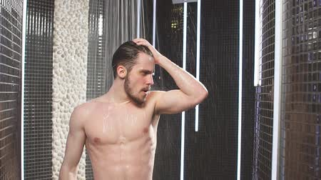 naga : Nude man relaxing while having the shower. get energy from water. Slow motion.