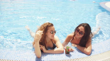 kypr : Couple of joyful girlfriends refreshing themselves in cool swimming pool in a hot sunny day. beauty and youth of pretty women in swimming pool at Luxury Hotel