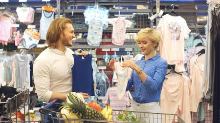 vállfa : Adorable young couple of european appearance hold in hands infant clothes in the big apparel store, deciding what is the best gift for newborn nephew.