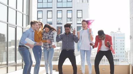 mobile music : Group of multi ethnic young friends dressed in casual cloth having fun on lounge outdoor area on the roof of office glass building